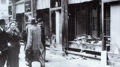 People walk past the broken windows of a Jewish-owned shop in Berlin. Over the course of two days, 91 Jewish people were killed and more than 1,000 synagogues and 7,500 businesses were destroyed.