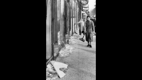 """A young man prepares to clean up broken window glass in Berlin. During """"Kristallnacht,"""" about 30,000 Jewish men between the ages of 16 and 60 were arrested and taken to concentration camps."""
