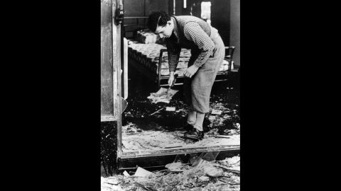 A young man clears broken glass from a Jewish-owned shop in Berlin.