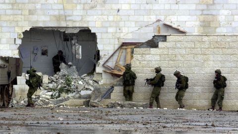 Israeli soldiers enter Arafat's West Bank headquarters in Ramallah on March 29, 2002. Tanks surrounded Arafat's compound earlier in the day in retaliation for a wave of recent suicide bombings. It was the beginning of a month-long siege.