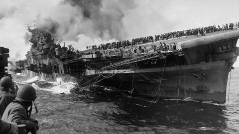 """The Essex-class USS Franklin burns after being hit by a Japanese dive bomber in 1945. The ship was named after Benjamin Franklin and nicknamed """"Big Ben."""""""