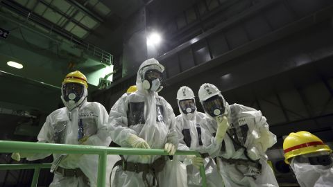 Members of the media wearing protective suits and masks look at the spent fuel pool from a fuel handling machine inside the building housing the Unit 4 reactor at the Fukushima Dai-ichi nuclear power plant in Okuma, Fukushima Prefecture, Japan, Thursday, Nov. 7, 2013.