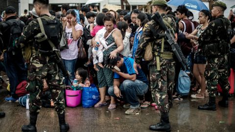 A woman comforts a crying relative as a plane leaves the airport during evacuation operations in Tacloban, Philippines on Tuesday, November 12.