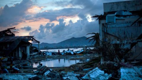 Survivors walk through the ruins of their neighborhood outside Tacloban on November 13.