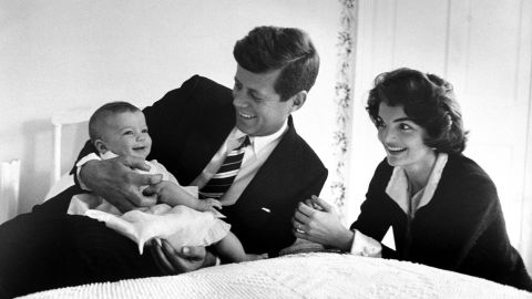 The Kennedy's cuddle daughter Caroline while relaxing on a bed at home on March 25, 1958.