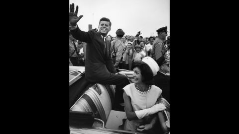 Shortly after his acceptance of the Democratic Party nomination for president, Kennedy and his wife smile and wave from the back of an open-top car in Massachusetts in July 1960.