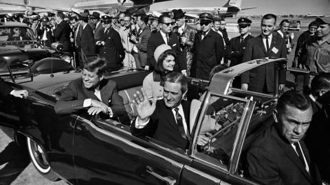 About 11:45 a.m., Texas Gov. John B. Connally Jr., waving to the crowd, and the Kennedys depart Love Field for a 10-mile tour of Dallas. The President asked about the weather earlier in the day and opted not to have a top on the limousine.