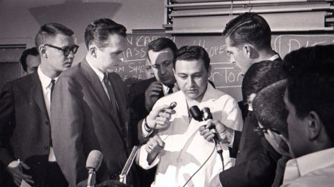 Before 1 p.m., Dr. Tom Shires, with Parkland public relations director Steve Landregan, rear, describes the President's wounds to the press. Four doctors worked on the stricken Kennedy in the emergency room.