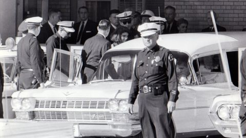 """After 2 p.m., Jacqueline Kennedy leaves Parkland Hospital with her slain husband's body. She would ride in the back with the bronze casket. """"I had a feeling that if somebody had literally fired a pistol in front of her face that she would just have blinked,"""" said Dallas Police Officer James Jennings, who helped put the casket in the hearse."""