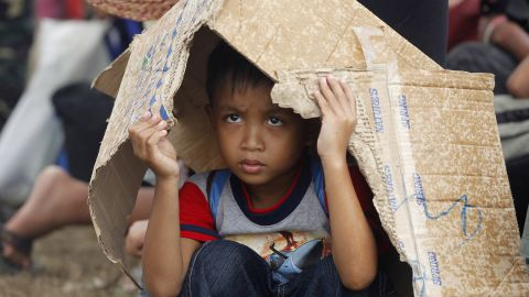 A boy takes cover from rain while waiting for an evacuation flight from Tacloban's airport November 14.