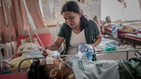 A typhoon survivor keeps her husband alive by manually pumping air into his lungs after his leg was amputated at a Tacloban hospital November 15. The hospital has been operating without power since the typhoon.