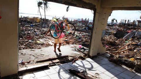 A man carries a bicycle as he walks through the ruins of a Tacloban building November 16.