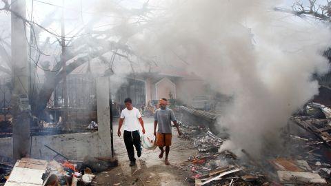 Men walk through smoke as they burn debris from a Tacloban church on November 16.