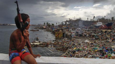 A boy holding a toy machine gun sits Sunday, November 17, on a ship that ran aground in Tacloban.