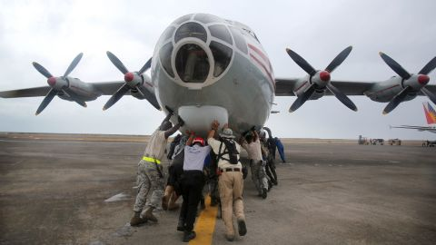 U.S. Navy personnel and other volunteers push a Russian cargo plane off the tarmac to make way for other aircraft November 17 in Tacloban.