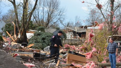 A police officer talks with a resident in Pekin after a tornado touched down in the area on November 17.