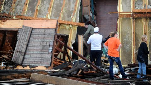 Tornado victims sift through an overturned mobile home in Brookport, Illinois, on November 17. A tornado ripped through the small town in southern Illinois.