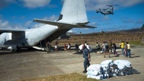Filipinos board an HC-130 Hercules airplane as U.S. sailors carry relief supplies November 17 in Guiuan.
