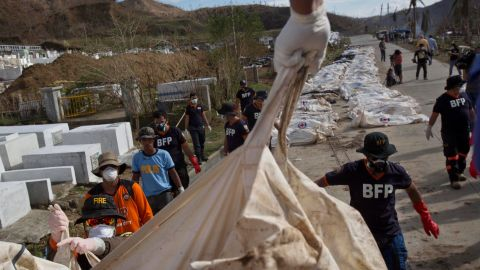 Firemen unload bodies November 19 for forensic experts to register and bury in a mass grave outside of Tacloban.