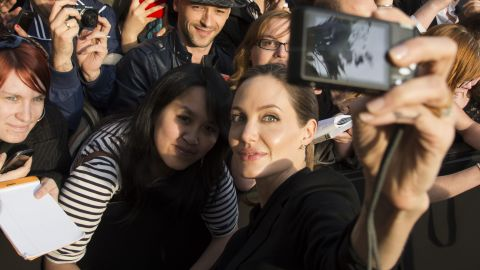 """Actress Angelina Jolie takes a photo of herself with a fan's camera at the Paris premiere of """"World War Z."""""""
