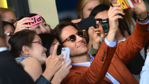 """Actor Bradley Cooper poses for selfies with eager fans at the Los Angeles premiere of """"The Hangover Part III."""""""