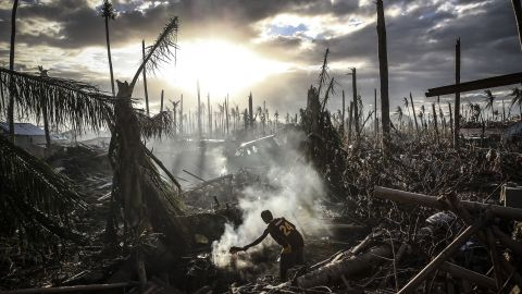 A man fans the flames of a fire in Tanauan, Philippines, on November 19.
