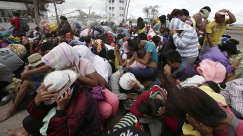 People at the airport in Tacloban react to a blast of wind from an aircraft on November 20.