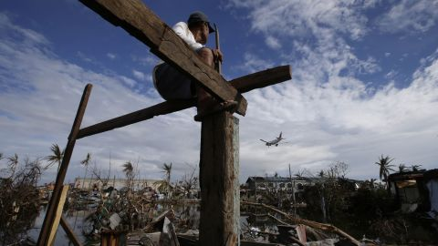 An airplane lands in Tacloban as Antonio Lacasa rebuilds his house on Thursday, November 21.