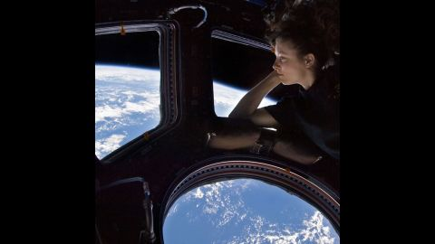 A throwback to 2010 for the International Space Station's 15th anniversary: NASA astronaut Tracy Caldwell Dyson looks down at Earth through a window on the ISS.
