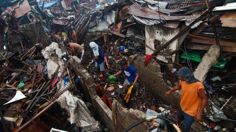 Groups of men clear debris near the shoreline on November 23 in Tacloban.