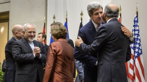 Iranian Foreign Minister Mohammad Javad Zarif talks with EU foreign policy chief Catherine Ashton as U.S. Secretary of State John Kerry embraces French Foreign Minister Laurent Fabius.