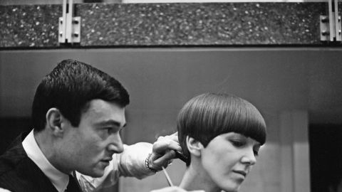 """Legendary hairdresser Vidal Sassoon applies the finishing touches of his trademark """"wedge bob cut"""" to miniskirt inventor Mary Quant. """"I was walking down Bond Street and there was a picture of a haircut that knocked me sideways. I knew I wanted <em>my </em>hair cut like <em>that,"""" </em>says Quant."""