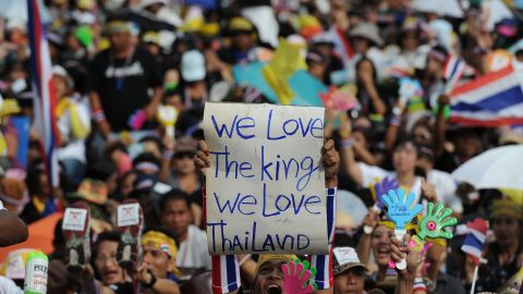 A Thai opposition protester holds up a sign during a rally at Democracy Monument in Bangkok on November 24, 2013. Organisers said 100,000 anti-government protesters had gathered, while thousands of pro-government 'Red Shirts' were expected to mobilise later at a suburban football stadium in support of Prime Minister Yingluck Shinawatra's crisis-hit administration. AFP PHOTO/Christophe ARCHAMBAULT (Photo credit should read CHRISTOPHE ARCHAMBAULT/AFP/Getty Images)