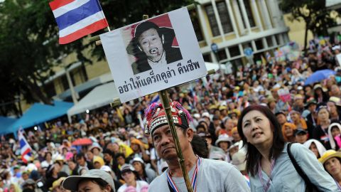 A Thai opposition protester holds up a placard mocking exiled former leader, Thaksin Shinawatra. Thaksin has a strong support base among Thailand's rural and working class, but is detested among the elite and middle classes, who accuse him of corruption.
