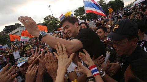 Democrat Party leader Abhisit Vejjajiva waves to anti-government protesters Sunday.