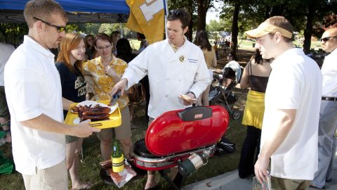 Jessica Keesee, center left, and her husband, Christian Pierce, center, serve up lunch from the grill as they tailgate at Georgia Tech.