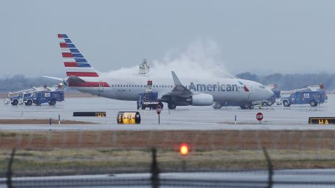 Employees at Dallas-Fort Worth International Airport de-ice a plane before departure on Monday, November 25.
