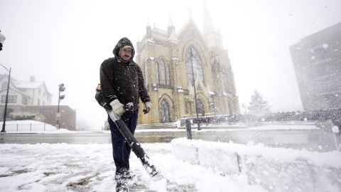 Mark Swigart uses a leaf blower to remove snow from the sidewalks November 26 in Pittsburgh.