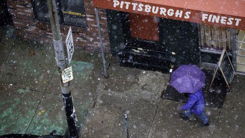 A pedestrian walks through snow showers along Penn Ave in Pittsburgh on November 26.