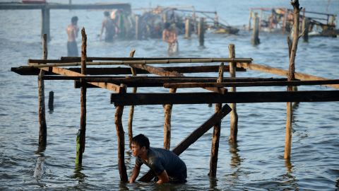 A man reconstructs his house in the bay of Tacloban, Leyte province, Philippines, on Wednesday, November 27, 2013.