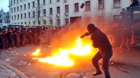 """A protester throws stones toward riot police on December 1. The crowd chanted """"Revolution"""" and """"Down with the Gang"""" as it gathered in Independence Square."""