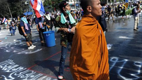 A Thai Buddhist monk watches as opposition protesters clash with police outside Government House in Bangkok on December 1, 2013.