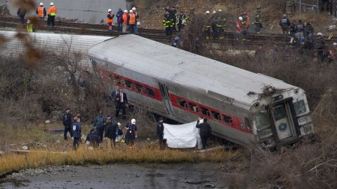 First responders and others work at the scene of the derailed train December 1. The train came off the tracks just as it was coming around a sharp curve.