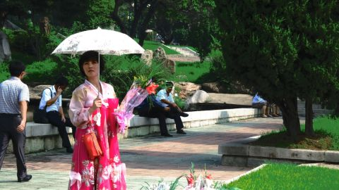 A flower vendor beside a Kim Il Sung statue in Pyongyang sells bouquets of flowers to locals and tourists to lay at the foot of the statue.