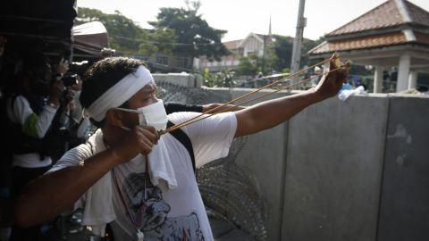 A protester aims a slingshot at riot police December 2 in Bangkok.