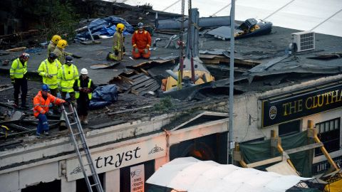 Rescuers work to lift the police helicopter wreckage from the roof of the pub on December 2.