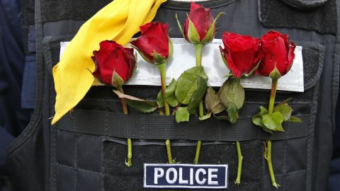 A police officer wears flowers offered by protesters in his bulletproof vest in Bangkok on December 3.