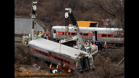 NEW YORK, NY - DECEMBER 2 :  Cranes lift the derailed train wagons near the Spuyteh Duyvil station on December 2, 2013 in New York City . The Metro-North passenger train derailed en route to New York City near the Spuyten Duyvil station, killing four people and wounding 63 others on December 1, 2013 in the Bronx borough of New York City. (Photo by Cem Ozdel/Anadolu Agency/Getty Images)