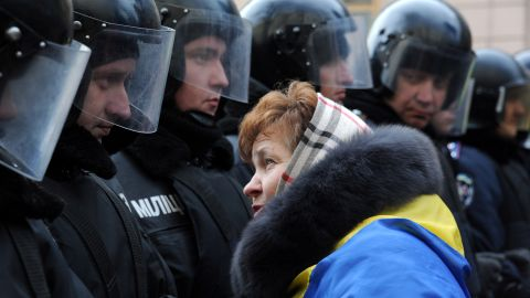 A protester faces riot police on December 3, 2013 as thousands rally outside the Ukrainian parliament in Kiev