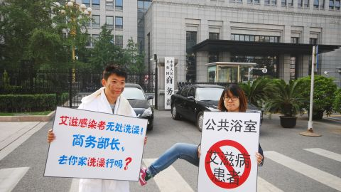 """Activist Liu Shi, left, stages a protest after a proposal to ban HIV/AIDS sufferers from entering bathhouses. His sign reads: """"HIV carriers have no place to bathe. Commerce minister, can we take a bath at your home?"""""""